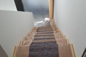 Sorgfältige Abdeckung des Treppenhauses vor dem letzten Anstrich.